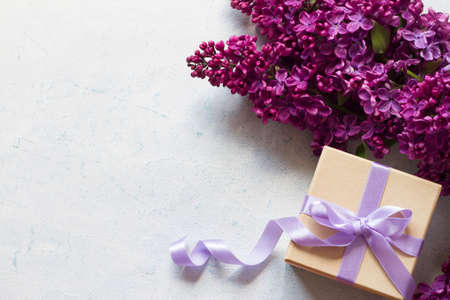 Gift box with lilac ribbon and lilacs flowers