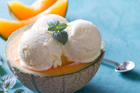 Delicious ice cream with mint leaf in melon bowl