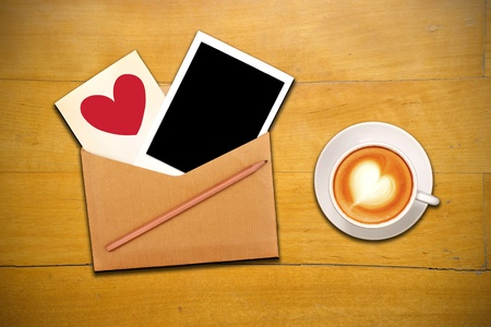 An open envelope with photo, pencil, red heart and cup of coffee photo
