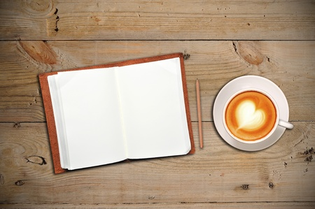 Open notebook with cup of coffee on a wooden floor photo