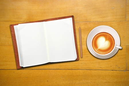 Open leather covered  book with blank page, coffee and pencil on old wooden table photo