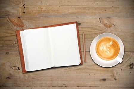 trompo de madera: Un cuaderno abierto con la taza de caf�
