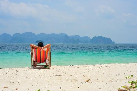 a man sitting on beach chair looking at sea photo