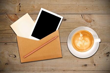 vintage envelope: Un envolvente de vintage con papeles y fotos dentro y una taza de caf� Foto de archivo