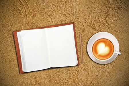 Open notebook with cup of coffee on sand photo
