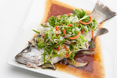 oriental cuisine: Fish in soy sauce, served on white plate