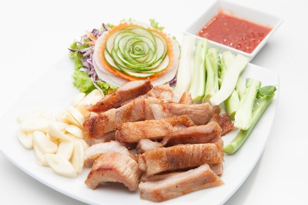 Fried pork served with various vegetables on white dish  photo