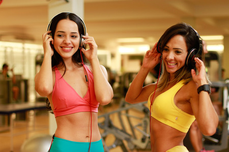 women listening music in gym photo