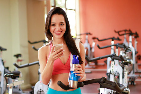 girl smiling with cell mobile in gym  photo