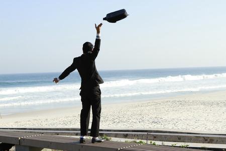 renounce: Business man throws bag of hand upward at the beach