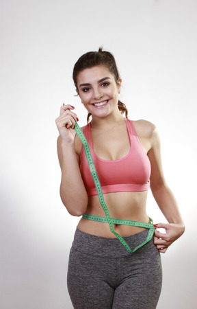 cordon tape: brunette woman measuring her belly with cordon tape