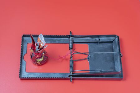 Candy as bait in a mousetrap. Red background