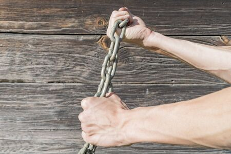 Mens hands tied with a metal chain