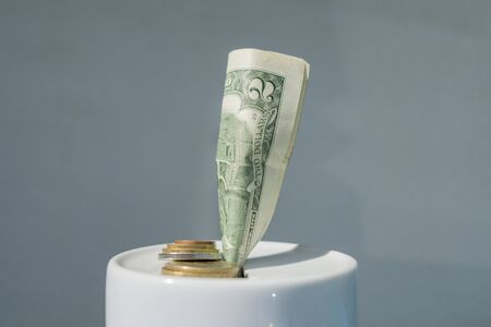 White porcelain piggy Bank with a two dollar bill Фото со стока