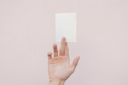 A young man holding a white blank sheet Archivio Fotografico - 137803865