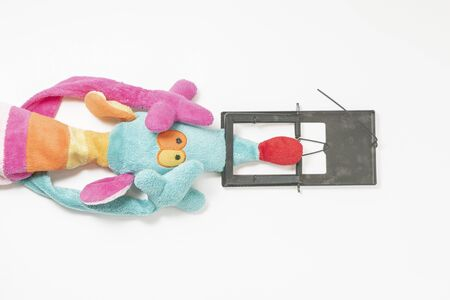 Collage of a toy mouse and a mousetrap. On white background