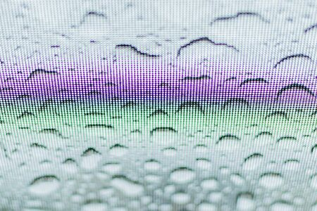 Rainbow on the glass hatch of the car with rain drops