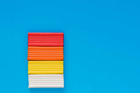 Children's plasticine of different colors on a blue background