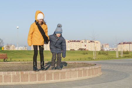 Teenage girl with younger brother walking in the new Park Stock Photo