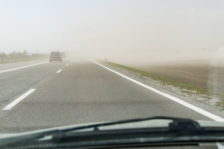 Strong wind carries sand across the highway road