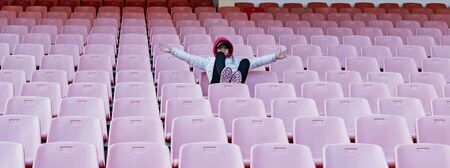 A young girl on the podium of an empty stadium Imagens