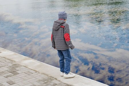A small boy walks along the embankment in the city Park