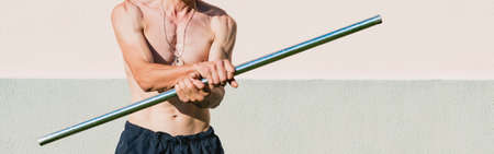 A middle aged man exercises with a metal pole 免版税图像