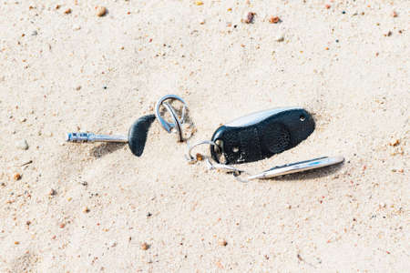 Car keys with keychain and alarm lost in the sand
