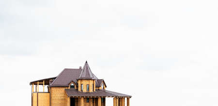 New large house made of wooden beams on a light background. The roof of metal