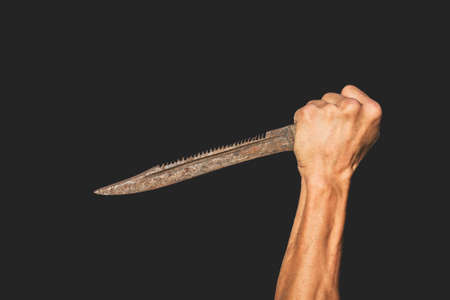An old rusty knife in the hand of an adult on a dark background 免版税图像