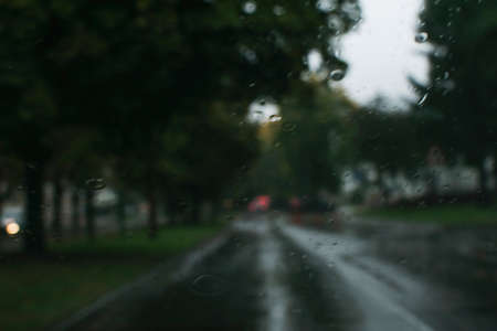 Blurry image through the car window. Autumn landscape of the city during the rain