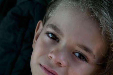 Brown eyes of a small boy in a dark room Archivio Fotografico