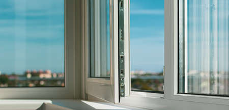 Sash plastic balcony window. The frame is white, the sash is slightly open. The sun's rays through the glass