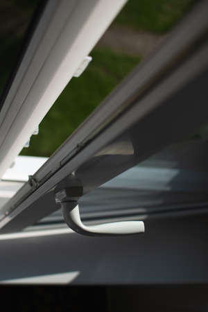 Handle sash plastic balcony window. The frame is white, the sash is slightly open. The sun's rays through the glass