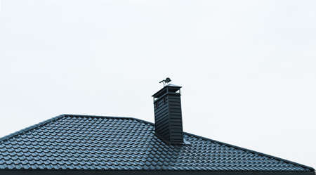 The metal roof of a newly built house is dark in color