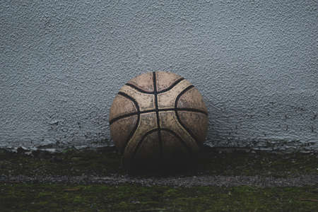 Old battered basketball on the background of the concrete wall of the house