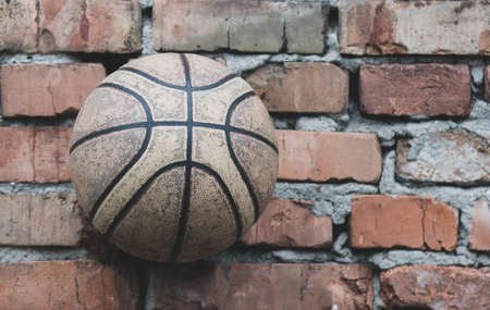 An old battered basketball against a brick wall