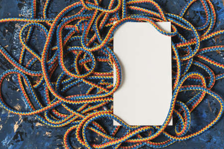 Nylon rope and white blank sheet for writing on a decorative wooden background of dark blue color Zdjęcie Seryjne