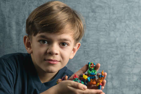 A little boy shows his crafts made of plasticine of different colors
