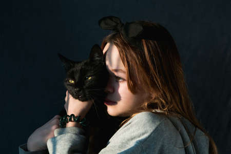 Young girl plays with a black pet cat during sunset 版權商用圖片