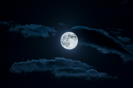 Full moon and white clouds on black night sky photo
