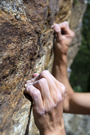 free climbing: hands of a man climbing on granite