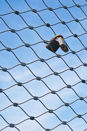 abandonment: Padlocks on metal mesh Stock Photo
