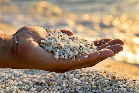 hand with quartz grain, Is Arutas Beach. Sardinia, Italy