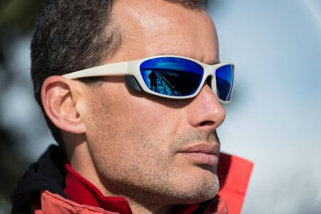 Man with sunglasses wearing mountain winter clothes