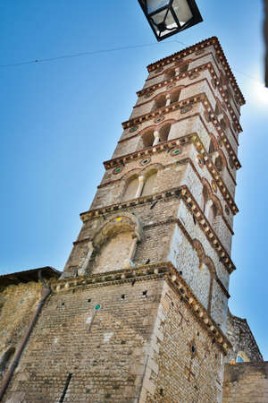 Beautiful upper part of decorated bell tower of Catholic Church or ancient Cathedral in the medieval small town Sermoneta Standard-Bild
