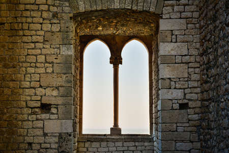 Medieval mullioned window with countryside at the horizon