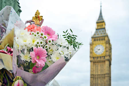 Flower tributes for the victims of the March 22,2017 terrorist attack at Westminster bridge, Big Ben and British Parliament