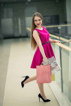comprando zapatos: Portrait of young happy smiling woman with shopping bags