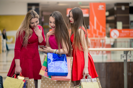 Happy Women with Smart Phone and Shopping Bags Stock Photo